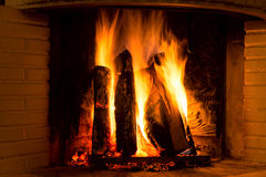 Burning fireplace with vertical firewood Royalty Free Stock Image