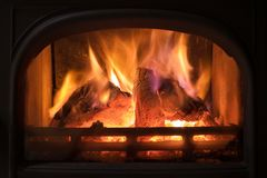 Burning fireplace with wooden logs burning inside. Warm light, r. Omantic, christmas like atmosphere stock images