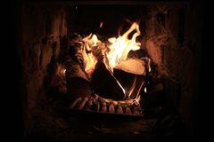 Burning firewood in a fireplace. Stock Photos
