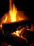 Burning firewood in a fireplace Stock Images