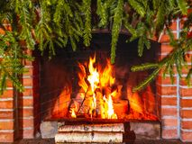 Burning firewood in a fireplace decorated for Christmas with branches of spruce stock photos