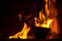 Burning firewood with flame tongues and spark in the fireplace stock photo