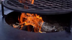 Burning firewood on the metallic grill on fresh air, close-up. Brazier with burning firewood. Tongues of flame, smoke, coal and ash. For cooking on the stock video footage