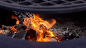 Burning firewood on the metallic grill on fresh air, close-up. Brazier with burning firewood. Tongues of flame, smoke, coal and ash. Cooking on the barbecue stock video