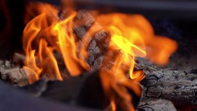 Burning firewood on the metallic grill on fresh air, close-up. Brazier with burning firewood. Tongues of flame, smoke, coal and ash. Cooking on the barbecue stock video footage