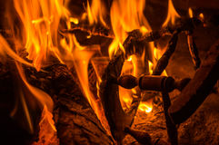 Burning firewood and a miniature wooden chair in the fireplace Stock Image