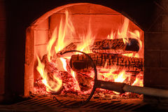 Burning firewood in traditional hearth furnace Stock Photography