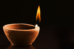 Burning Flame in Earthern Lamp. On Black Background royalty free stock photo