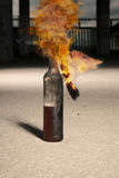 Burning flammable bottle on city ground. Flammable bottle known as molotov cocktail with rags burning on ground Stock Images