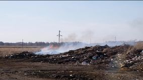Burning Garbage dump pollutes the environment. Strong wind rises toxic smoke of burning garbage into the air. stock footage
