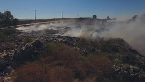 Burning Garbage Dump At Suburbs. AERIAL VIEW. Pan shot of a big garbage heap burning at suburbs producing smoke blown by the wind stock footage