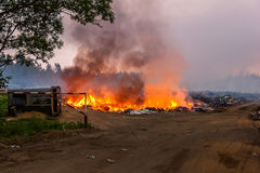 Burning garbage in the landfill solid waste. Fire. Burning garbage dump. Smoke poisons the district Stock Photography
