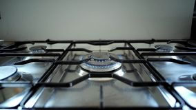 Burning gas in cooker hobs. Common top view on professional industral steel made cooker with five gas hobs starting to burn each after each in couse and turning stock footage