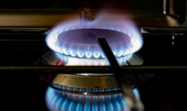 Burning gas stove blue flames close up in the dark on a black background. Image royalty free stock photography
