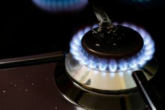 Burning gas stove blue flames close up in the dark on a black background. Image stock images