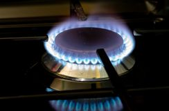 Burning gas stove blue flames close up in the dark on a black background royalty free stock photography