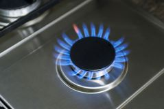Burning gas, gas stove burner, hob in the kitchen. Blue gas stove in the dark.  stock photo
