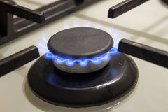 Burning gas stove hob blue flames close up in the dark on a blac Stock Image
