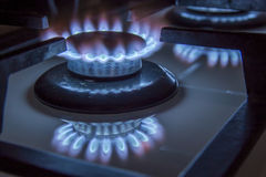 Burning gas stove hob blue flames close up in the dark on a blac Royalty Free Stock Photos