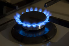 Burning gas stove hob blue flames close up in the dark on a blac Royalty Free Stock Photography