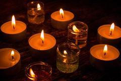 Burning gel and wax candles on a wooden Stock Images