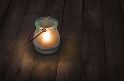 Burning glass lantern at night. On wooden background Royalty Free Stock Photo