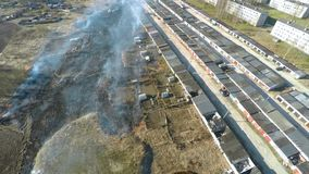 Burning grass at backyard. Garages. Aerial footage. stock video footage