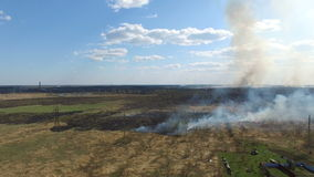 Burning grass near village stock footage