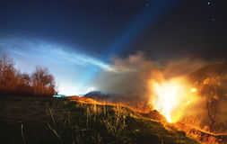Burning grass and trees in the gorge amidst the lights of the city and the starry sky, a night fire Stock Photos