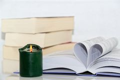 Burning green candle and book with heart shape. Burning green candle and open book with letters formed as heart against pile of books on white background stock images
