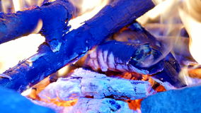 Burning hardwood in detail. Burning woods shiver in hot air and gentle flames  fluorescing.  White ash covers the burning pieces o stock footage