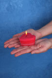 Burning heart-candle on the palms. Blue background Stock Images