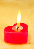 Burning heart shaped candle Stock Photos