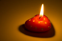 Burning heart shaped candle Stock Photo