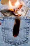 Burning a hole in my pocket 1. Concept image of money burning a hole in a jeans pocket royalty free stock images