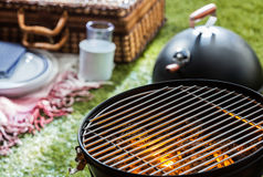 Burning hot fire in a portable barbecue. Close up of a burning hot fire in a portable barbecue with an empty grill and a wicker picnic hamper visible on a green Royalty Free Stock Photos