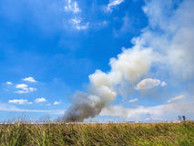Burning house causes a big pile of smoke. Black smoke rising up to blue sky background royalty free stock photography