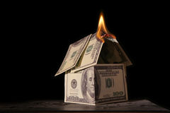 Burning house of dollars. On black stock images