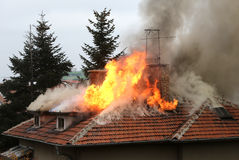 Burning house roof. A house roof on fire and smoke royalty free stock photography