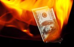 Burning a Hundred Dollar Bill. A hundred dollar bill on fire Stock Photo