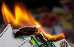 Burning hundred euro. A hundred euro bill in Europe currency is on fire Royalty Free Stock Images