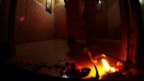 Burning icon-lamp and flowers on floor monk`s legs in temple near statue of Goddess evening ceremony