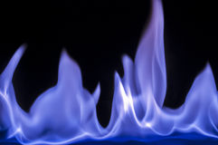 Burning ignited feul, fire,flames. Drops of flammable liquid ignited making blue flames Stock Image