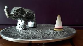 Burning incense cone next to an elephant figure royalty free stock photos