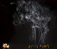 Burning incense cones with intense smoke on black background Stock Photo