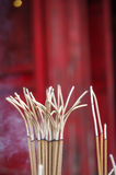 Burning incense. Lots of incense sticks burning with red background Stock Images