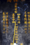 Burning incense stick. In front of chinese characters stock photography
