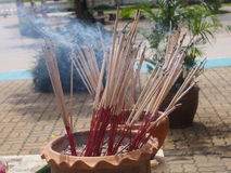 Burning incense sticks in ashes earthenware pot with waving smoking Stock Image