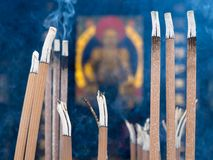 Burning incense sticks in a buddhist temple, blurred Buddha image in background royalty free stock photography
