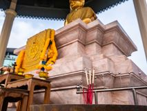 Burning incense sticks in front of the Buddha statue royalty free stock image